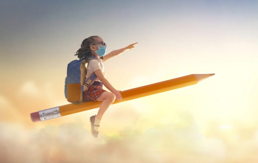 Back to school after quarantine! Happy cute industrious child with face mask flying on the pencil on background of sunset sky. Concept of education after pandemic. The development of the imagination.